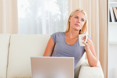 Woman having a coffee while holding a laptop in her living room photo