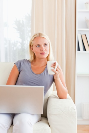 Portrait of a woman having a coffee while holding a laptop in her living room photo