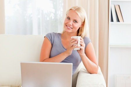 Woman having a coffee while holding a notebook in her living room photo