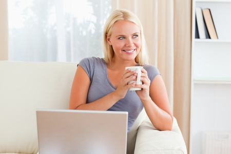 Woman having a tea while holding a notebook in her living room photo
