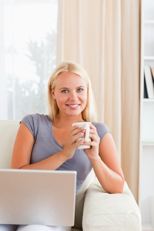 Portrait of a woman having a tea with a notebook in her living room Stock Photo - 11192134