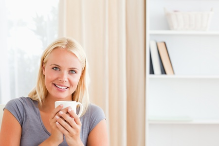 Woman sitting on a couch with a cup of tea in her living room photo