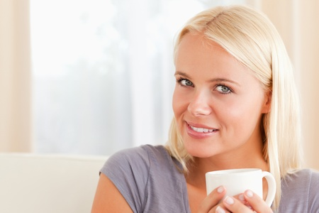 Close up of a woman sitting on a couch with a cup of coffee in her living room photo