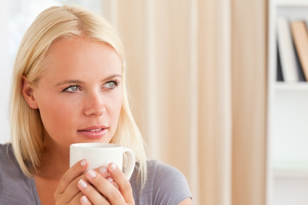 Close up of a woman sitting on a sofa with a cup of tea in her living room photo