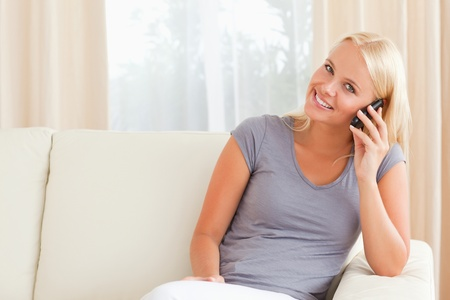 Smiling woman speaking on the phone in her living room Stock Photo - 11186770