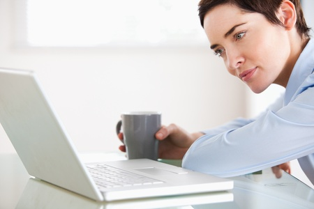 Brunette woman with a laptop and a cup in a kitchen photo