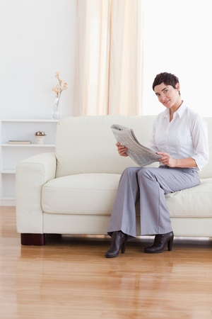 Gorgeous businesswoman reading the news in the living room photo