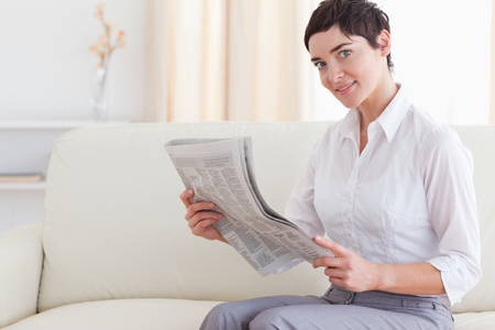 Beautiful brunette woman reading the news in the living room photo