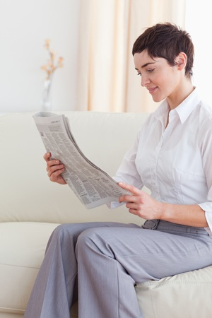 Portrait of a Beautiful brunette woman reading the news in the living room photo