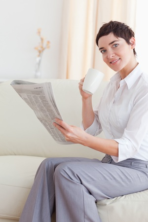 Portrait of a woman with a cup reading the news while looking at the camera in the living room photo
