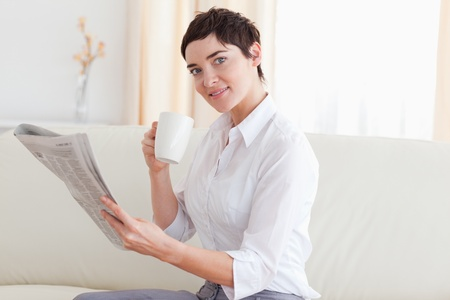 Woman with a cup reading the news while looking at the camera in the living room photo