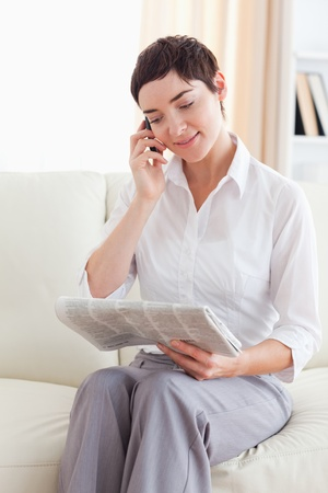 Woman with a cellphone and a newspaper in the living room photo