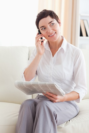 Brunette Woman with a cellphone and a newspaper in the living room photo