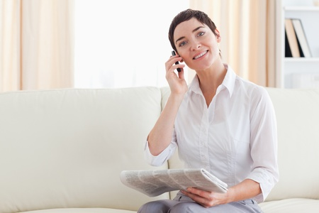 Smiling Woman with a cellphone and a newspaper in the living room photo