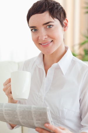 Charming woman with a cup and a newspaper in the living room photo