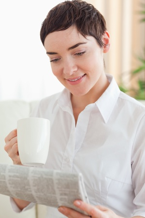 Cute woman with a cup and a newspaper in the living room photo