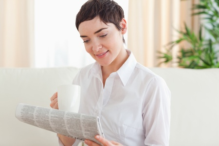 Brunette woman with a cup and a newspaper in the living room photo