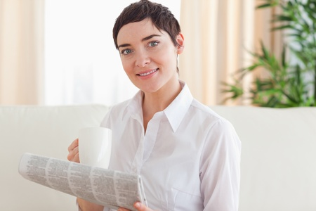 Portrait of a Brunette woman with a cup and a newspaper in the living room photo