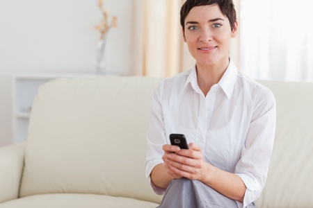 Portrait of a beautiful woman with a cellphone in the living room photo