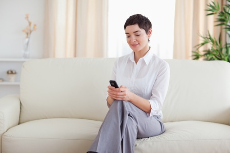 Woman sitting on a sofa with a phone in the living room photo
