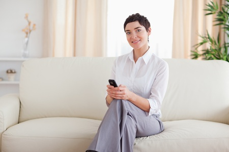 Cute Woman sitting on a sofa with a phone in the living room photo