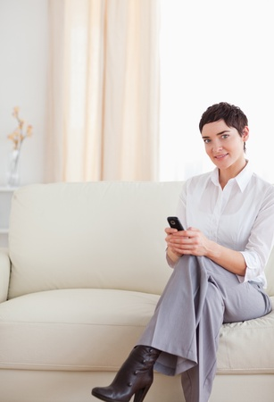 Charming Woman sitting on a sofa with a phone in the living room photo