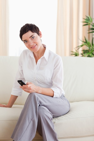 Brunette Woman sitting on a sofa with a phone in the living room photo
