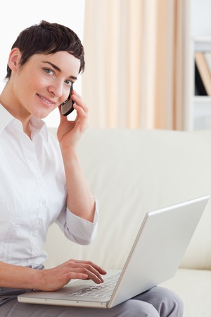 Short-haired woman with a laptop and a phone looking into the camera in the living room photo