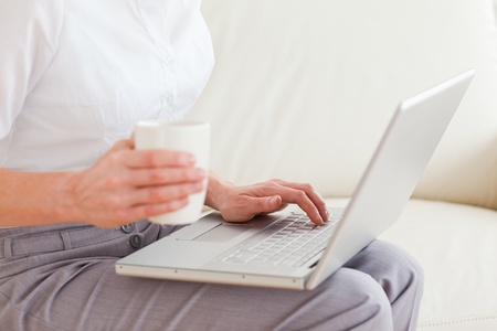Close up of a woman holding a cup having a notebook on her lap in the living room photo