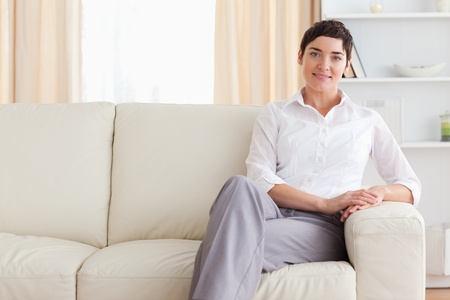 Smiling woman sitting on a sofa in the living room photo