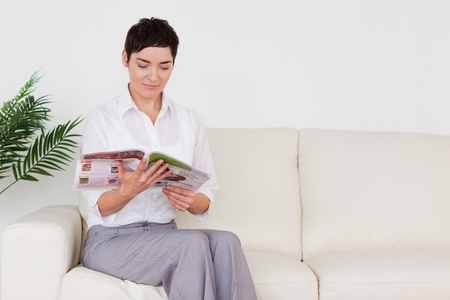 Beautiful brunette woman reading a magazine in a waiting room photo