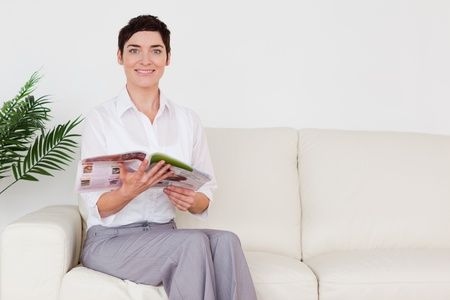 Brunette woman reading a magazine in a waiting room photo