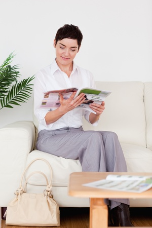 Charming woman reading a magazine in a waiting room photo