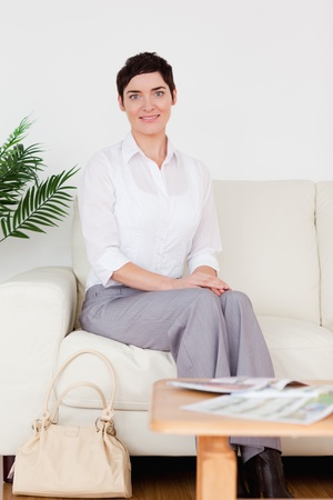 Cute short-haired woman sitting on a sofa in a waiting room photo