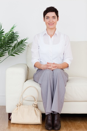Smiling short-haired woman sitting on a sofa in a waiting room photo