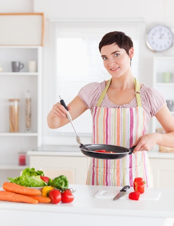 spatula: Beautiful woman cooking in the kitchen Stock Photo
