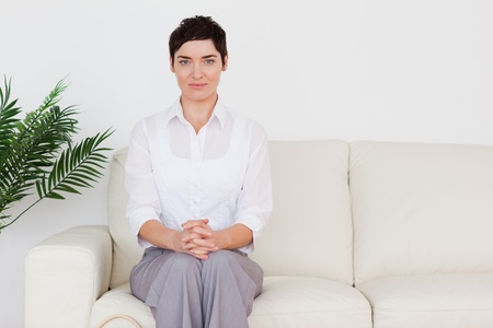 Brunette woman sitting on a sofa in a waiting room photo