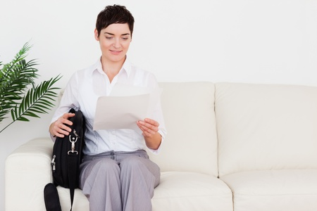 Businesswoman with a paper and a bag in a waiting room photo