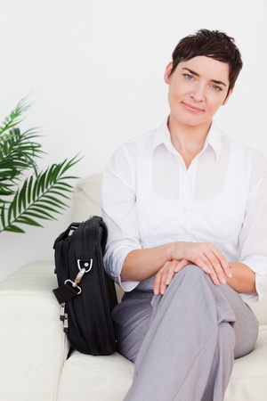 Smirking Businesswoman with a bag in a waiting room photo