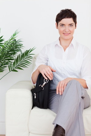 Short-haired businesswoman sitting on a sofa in a waiting room photo