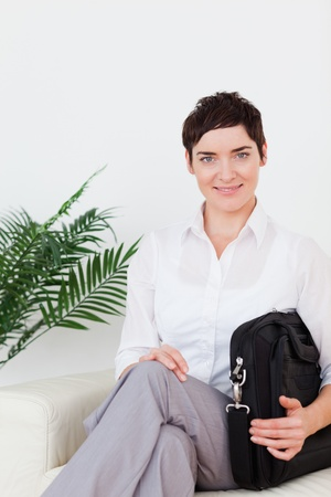 Short-haired smiling businesswoman sitting on a sofa in a waiting room photo