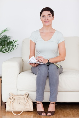 Smiling Woman with a bag and a magazine in a waiting room photo