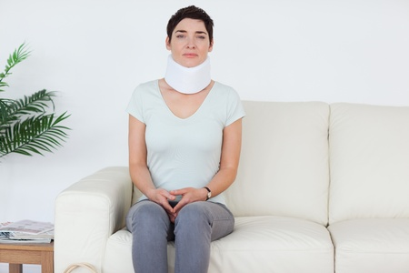 Sad Woman with a surgical collar in a waiting room photo