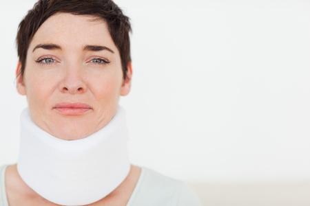 the neck: Primo piano di una donna triste con un collare chirurgico in una sala d'attesa