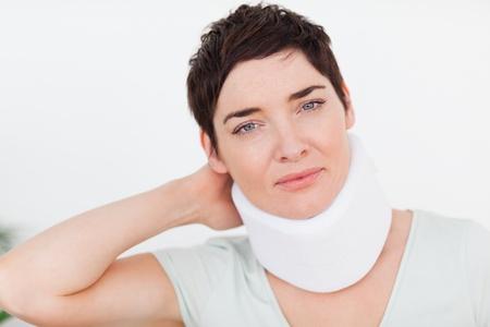Primer plano de una mujer con un collarín en una sala de espera