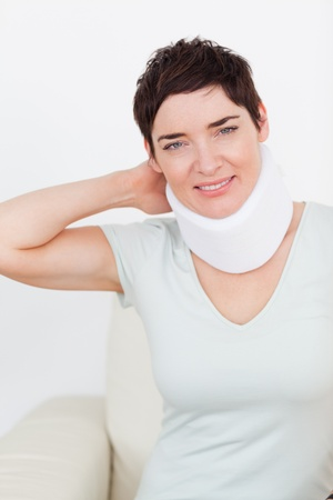 Close up of a brunette woman with a surgical collar in a waiting room photo