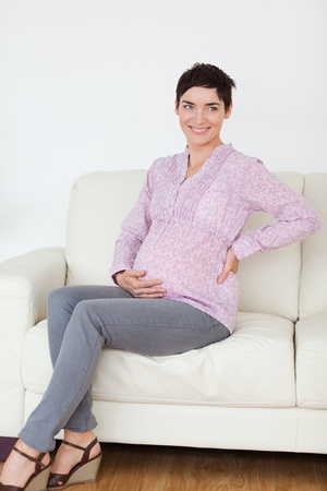 Pretty pregnant woman sitting on a sofa in a waiting room Stock Photo - 11190163