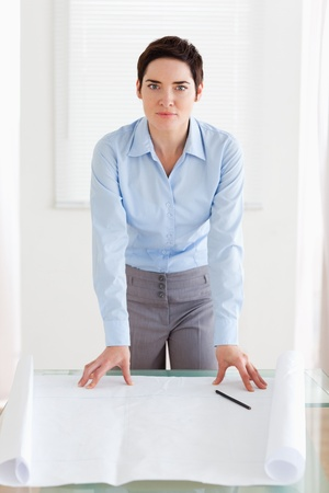 Businesswoman with a architectural plan in an office photo