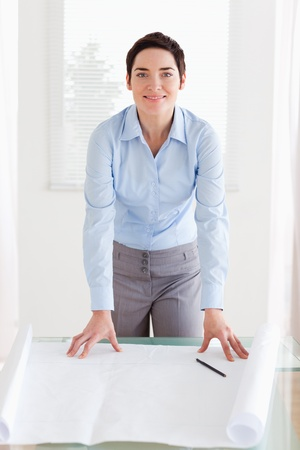 Smiling businesswoman with a architectural plan in an office photo