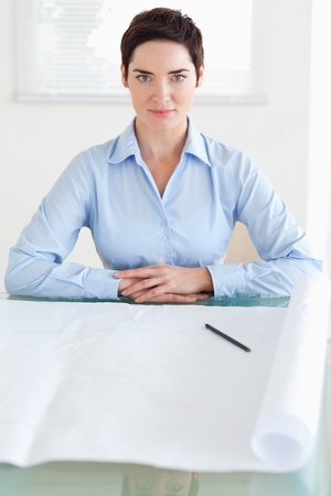Serious short-haired businesswoman with a architectural plan in an office photo